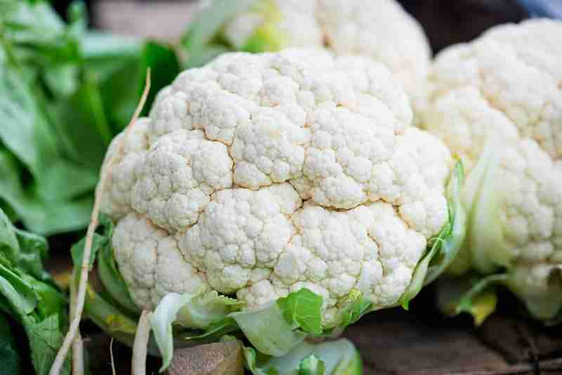 white cauliflower head shown close up with green leaves in the background