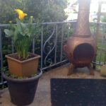 a copper coloured chiminea sitting on a patio with iron railing behind and flowers to the side