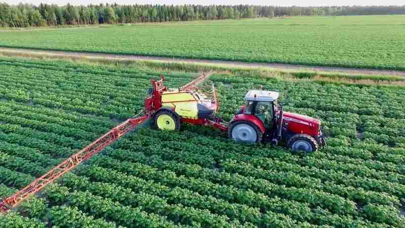 a crop sprayer pulled with a tractor spraying a field of potatoes