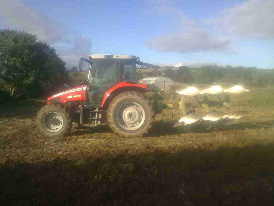 A tractor with a plough on behind in a field