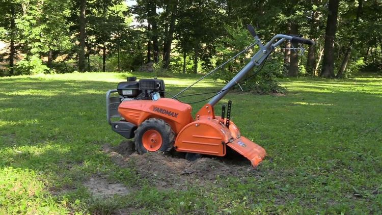 yardmax heavy duty rototiller sitting on garden grass with a tree in the background