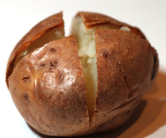 a ccoked baked potato cut into quarters at the top with a white background