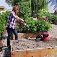 small tiller cultivator working in a raised bed with a woman pushing it and plants in the background
