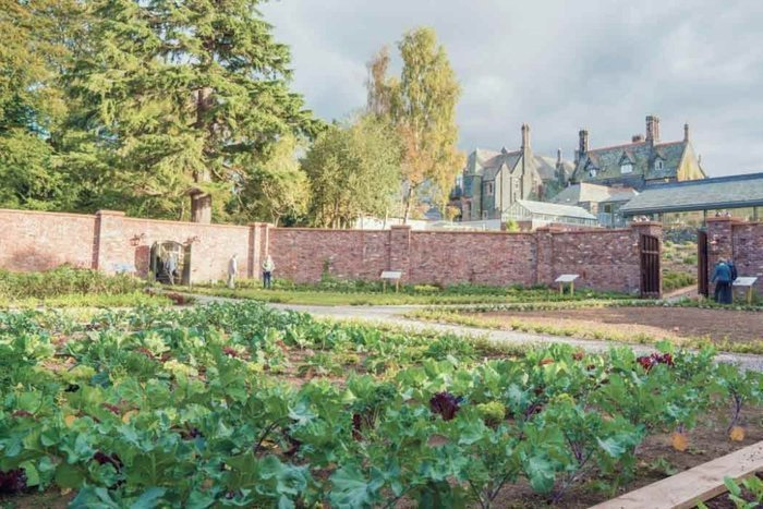 walled garden with brick wall and vegetables growing inside and a large house in the background