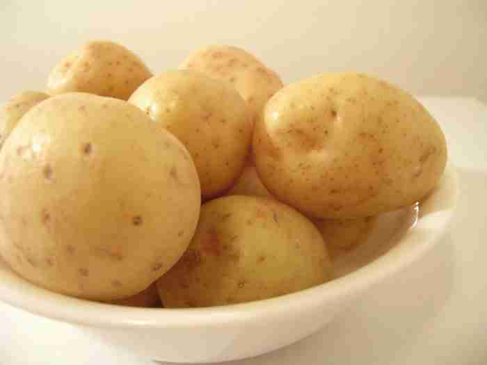 bowl of boiled white potatoes with skins on