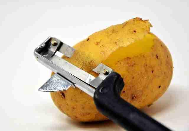 A raw potato being peeled