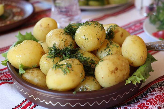 a bowl of boiled potatoes with dill on top