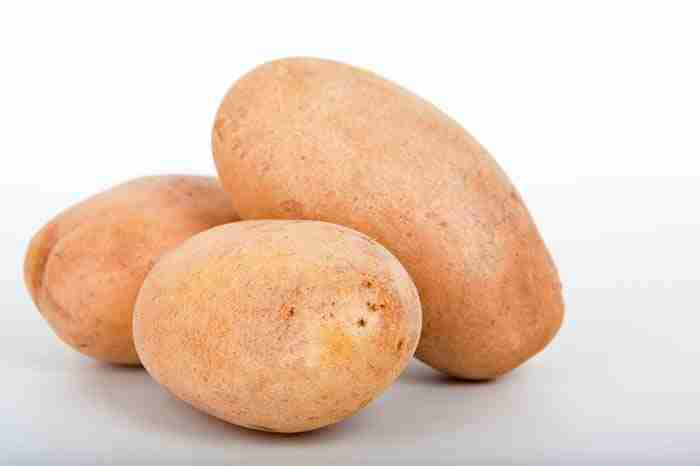 three uncooked oval shaped  potatoes on a white background