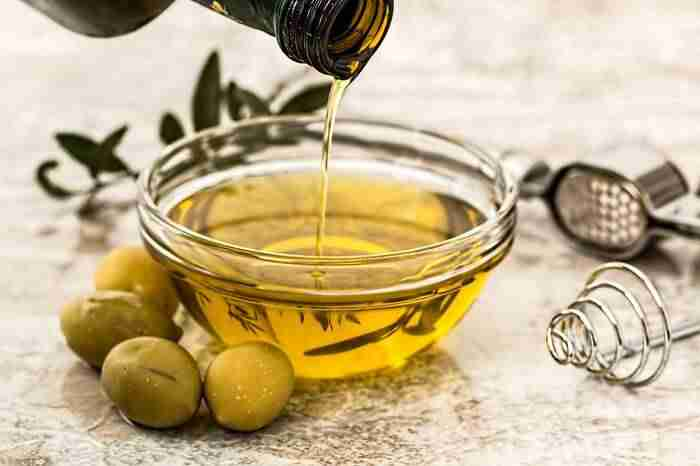 olive oil being poured out of a bottle into a glass bowl