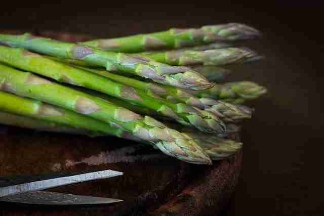 Asparagus stems on a wooden chopping board