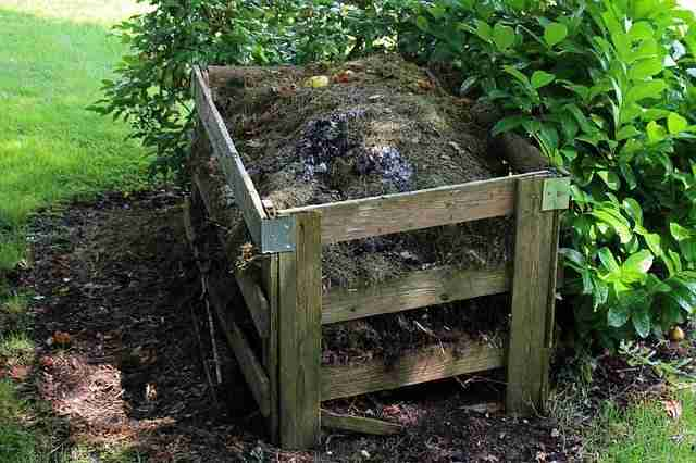 typical wooden board homemade compost heap filled with organic material