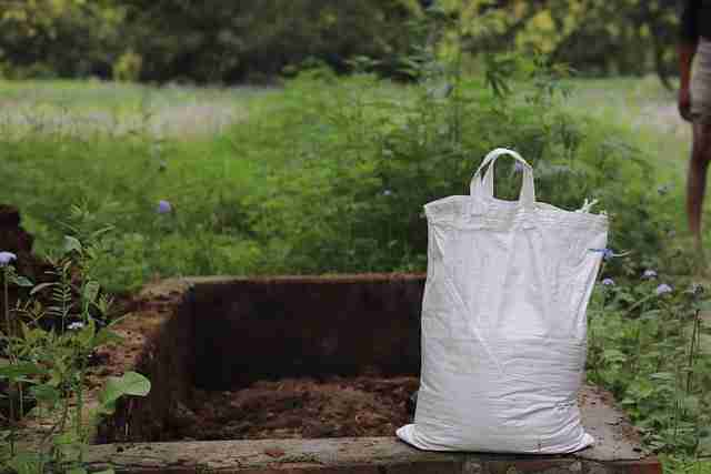 compost heap with a bag of compost filled to be taken away