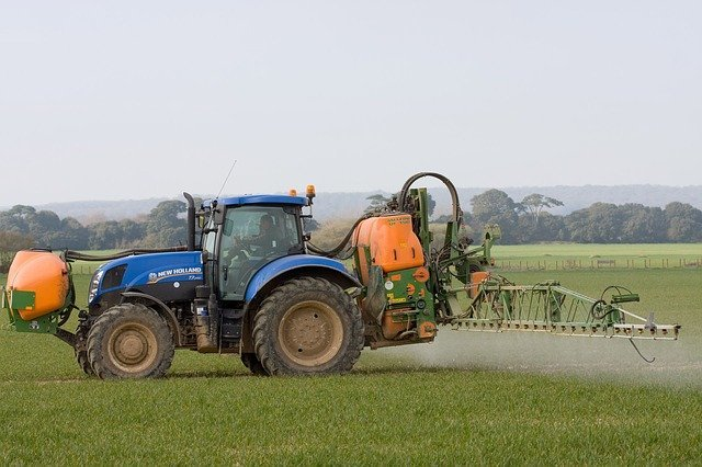 tractor and sprayer spraying crops