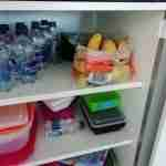 a plastic bag of potatoes sitting in an apartment kitchen cupboard